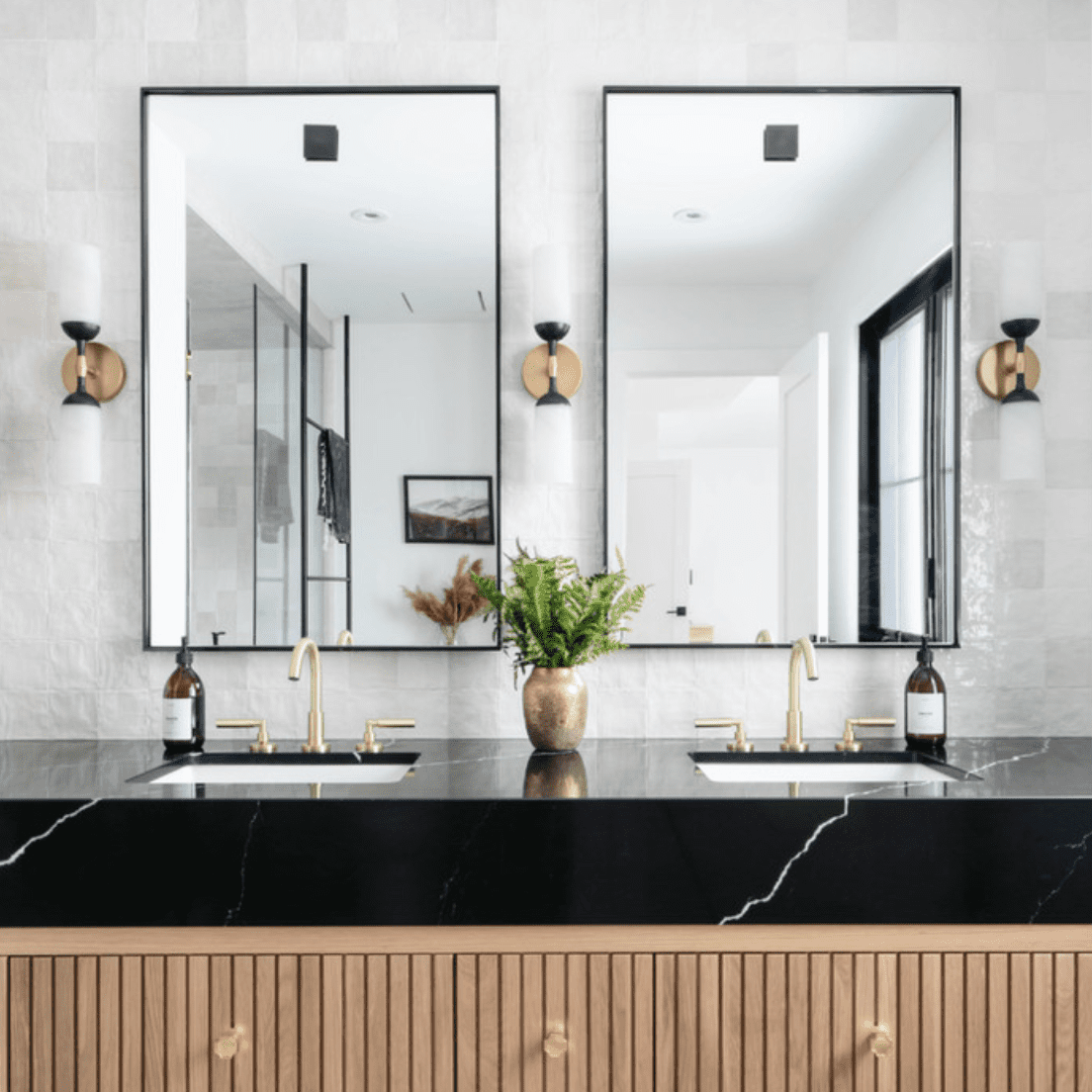 A bathroom with two mirrors, a shiny white backsplash, black marble countertops, and wood cabinets
