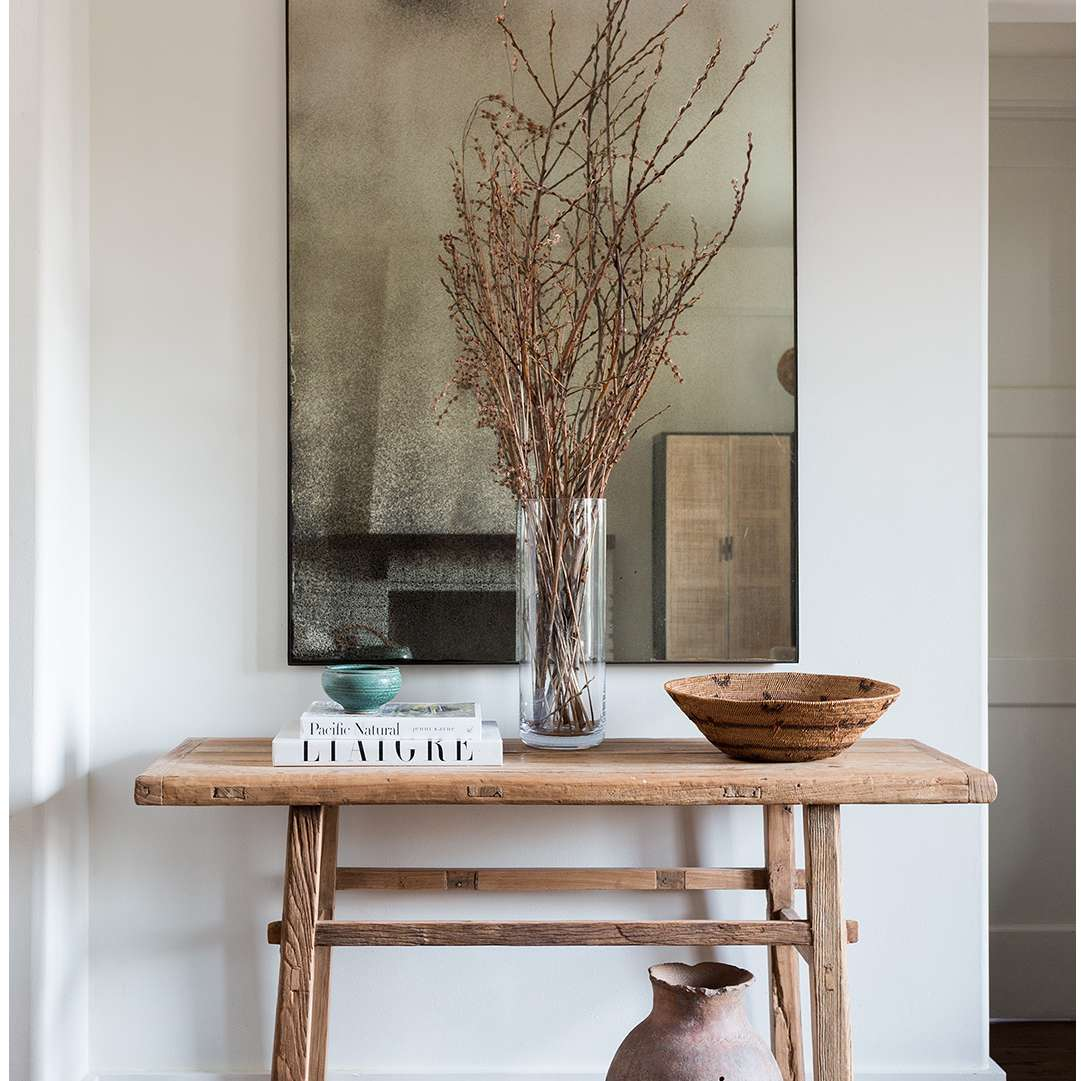 Wood console with vignette of ceramic vase, wooden bowl, and stack of books