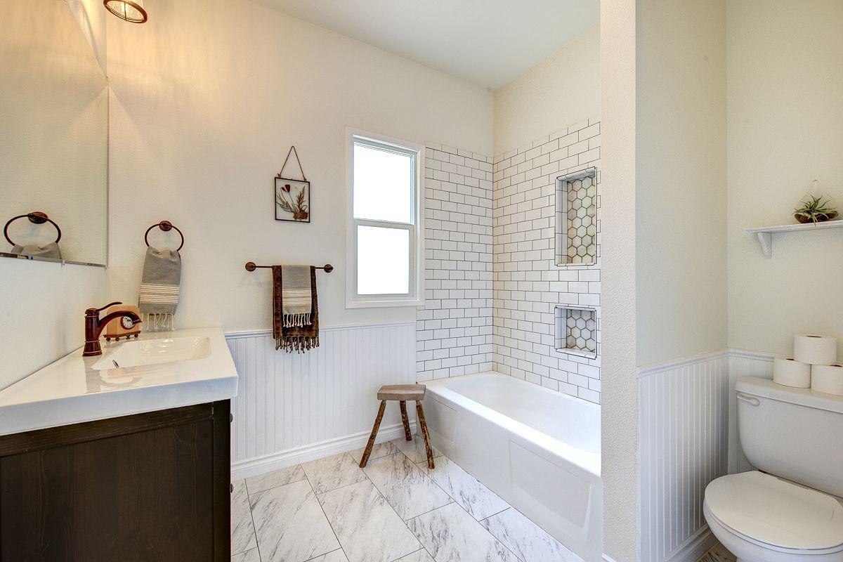 White beadboard bathroom with subway tile shower.