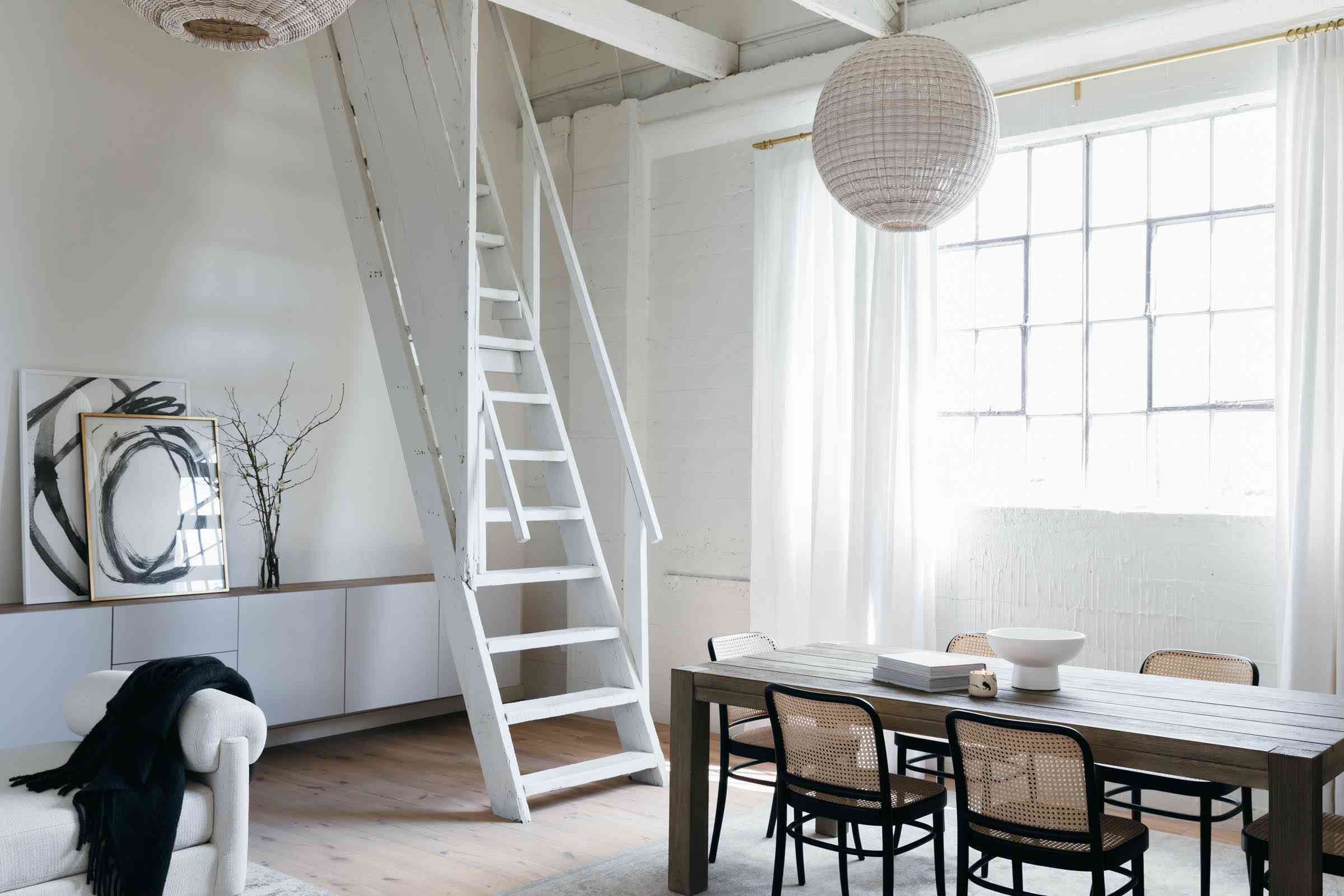 An industrial living space that has been painted white and adorned with white decor