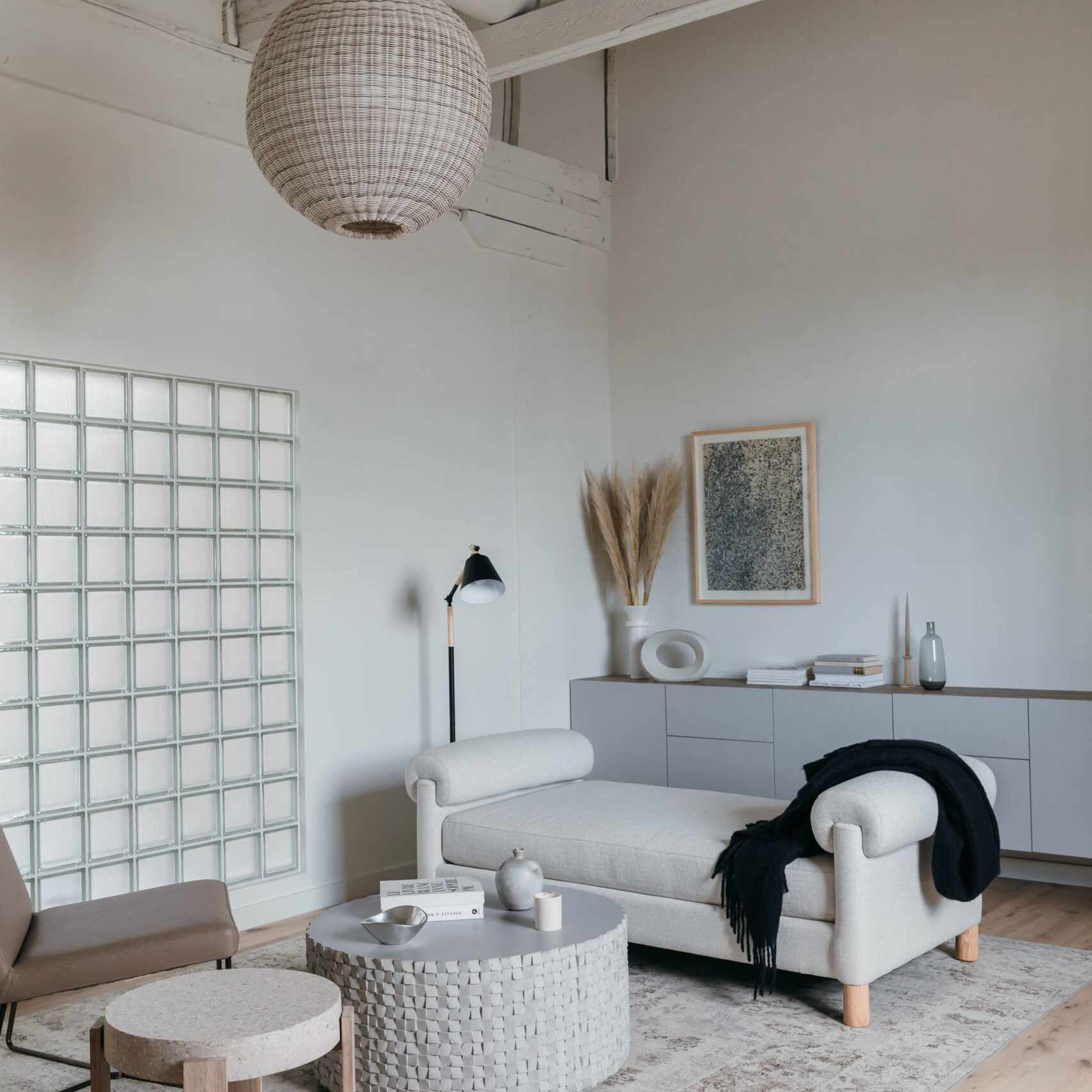 A living room with white walls and exposed ceilings
