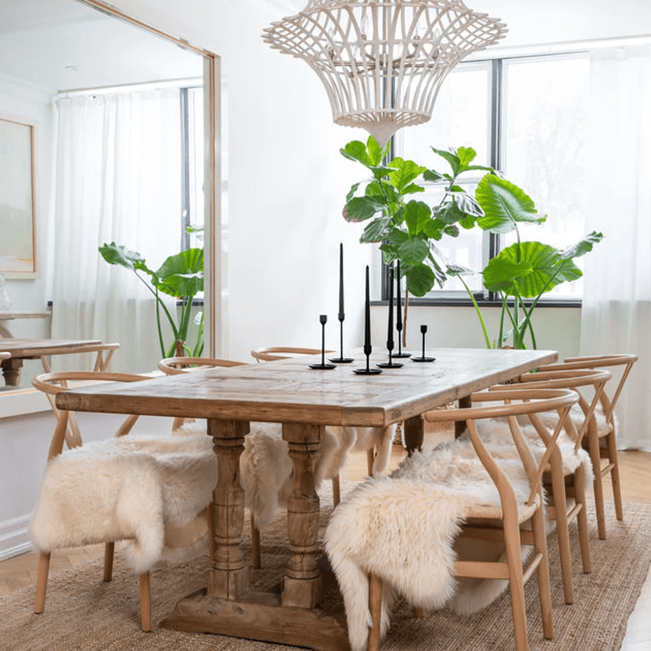 A dining room with a white woven chandelier that complements the decor in the room