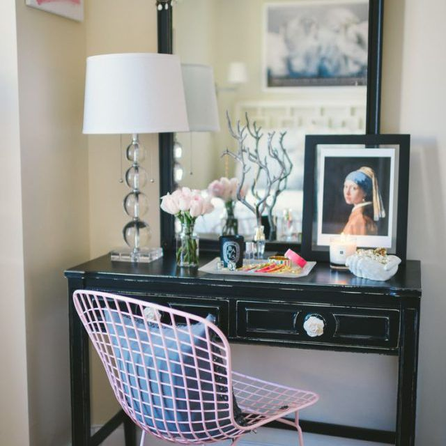 Black vanity with fun pink chair and decor.