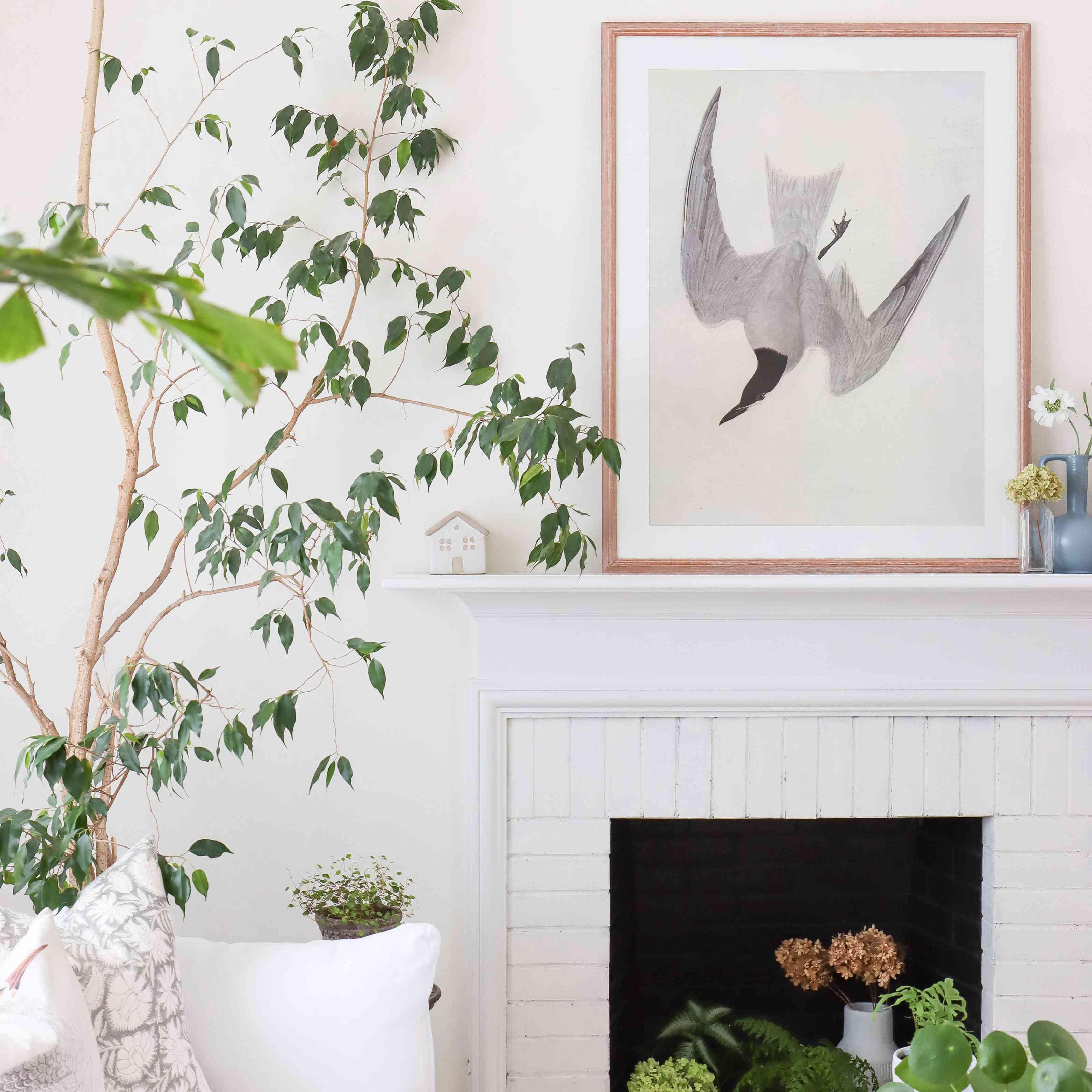 Large art piece of a bird above a fire[lace mantel.