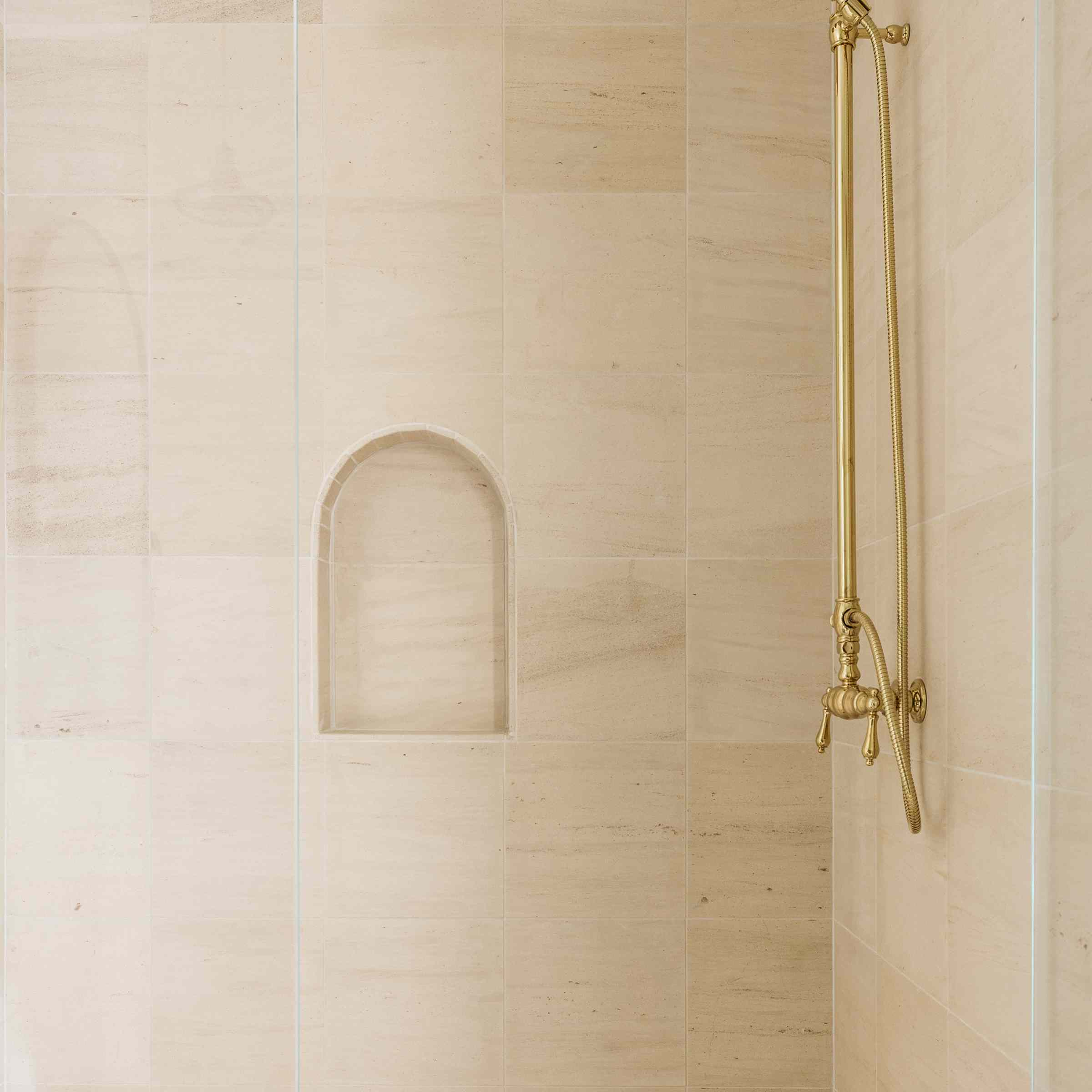Brett Foken home tour - shower with gold hardware and light pink stone