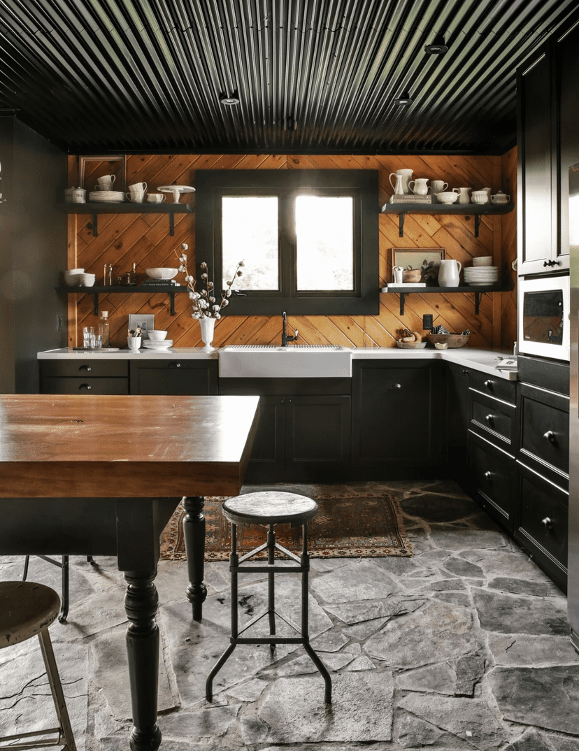 A cozy kitchen with black ceilings and stone-lined floors