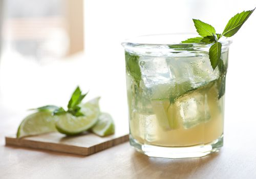 Vodka cocktail in a glass with mint and lime garnish.