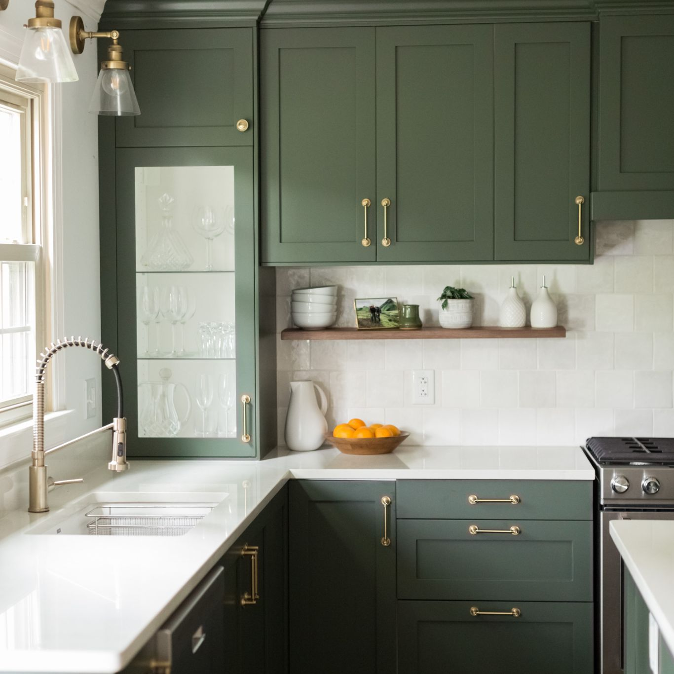 A kitchen lined with forest green IKEA cabinets