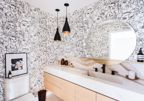 Bathroom with black and white printed wallpaper.