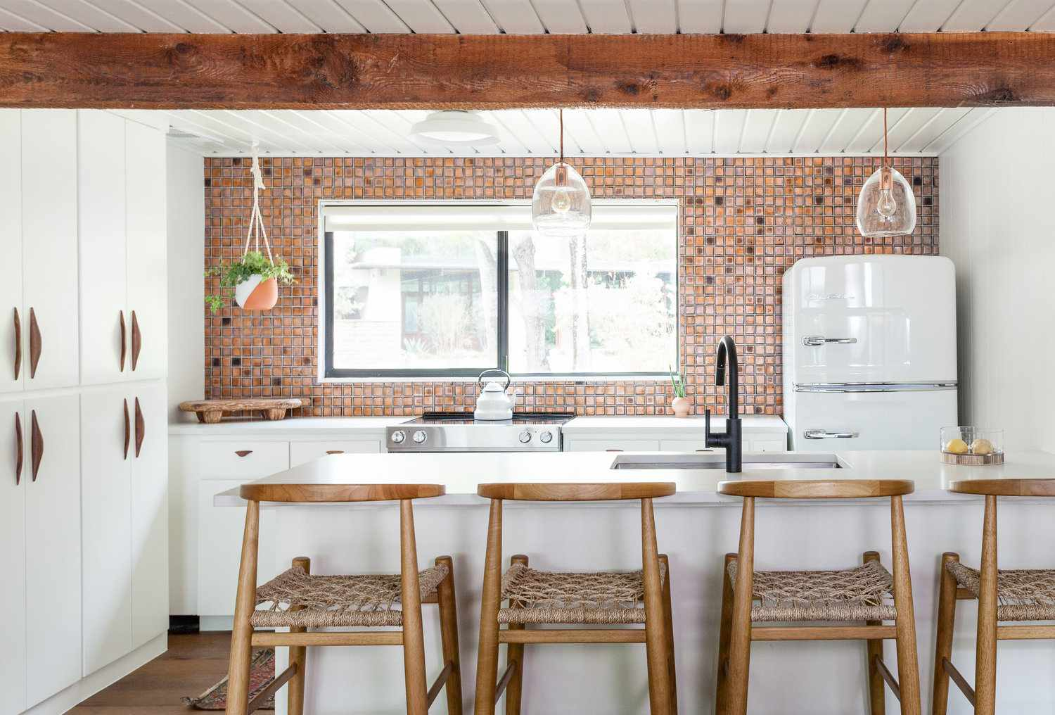 A kitchen backsplash lined with a varied array of small copper tiles