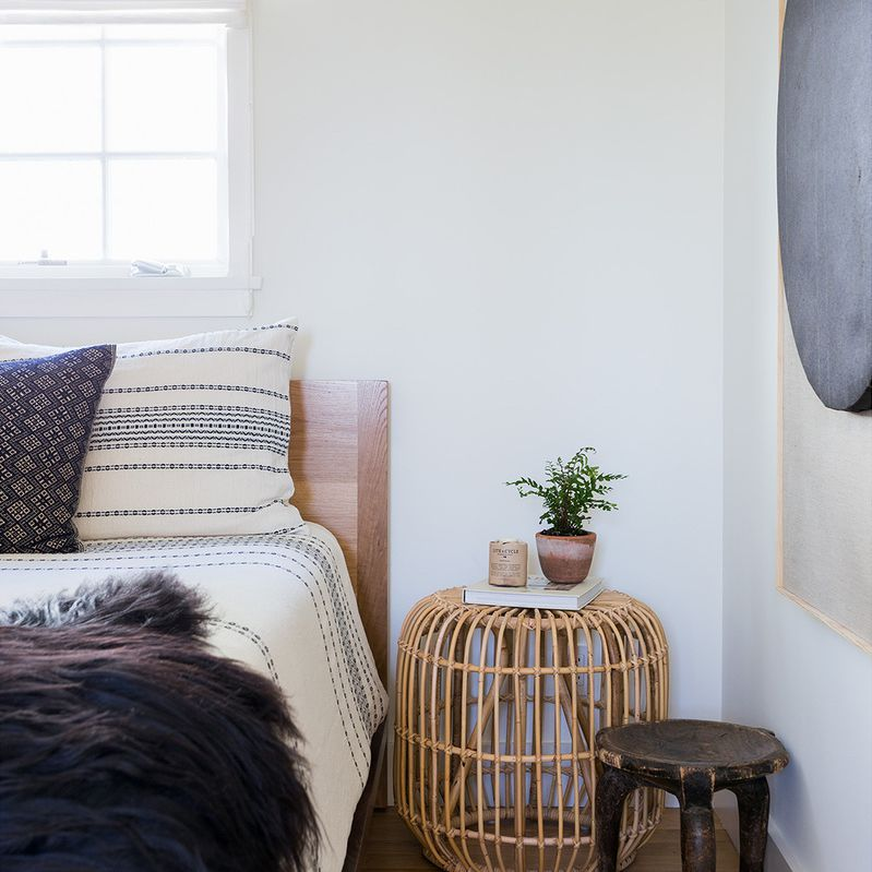 Boho chic bedroom with rattan side table and aged wood stool