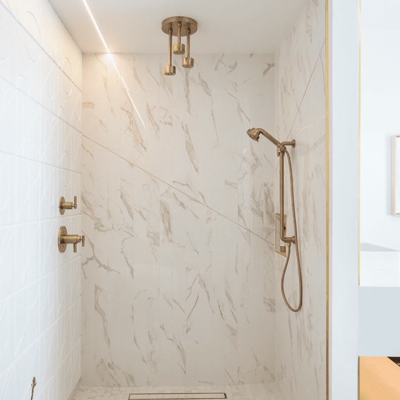 A shower lined with textured white marble