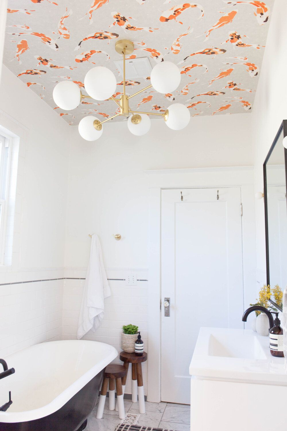 bathroom with wallpapered ceiling and stand alone tub