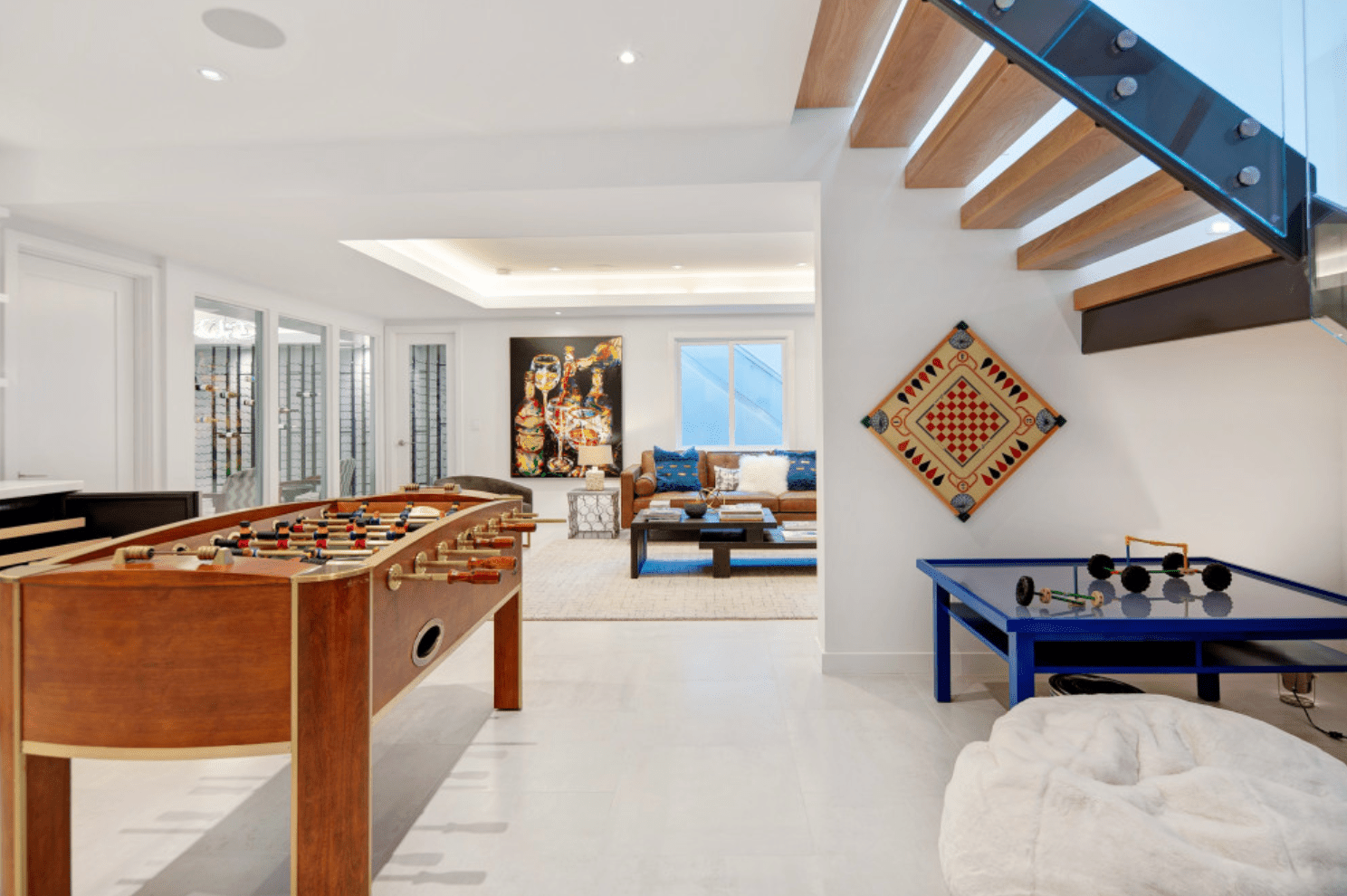 A well-lit basement with a recessed ceiling lined with cove lighting