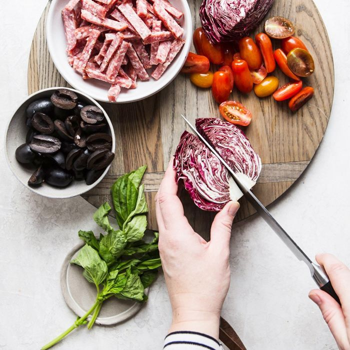 Plate of meats, fresh produce, and herbs