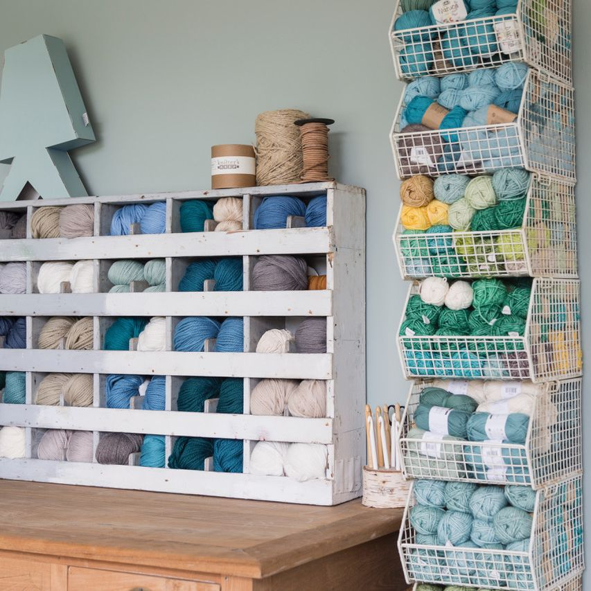 A color-coordinated craft room filled with blue and neutral-colored yarn