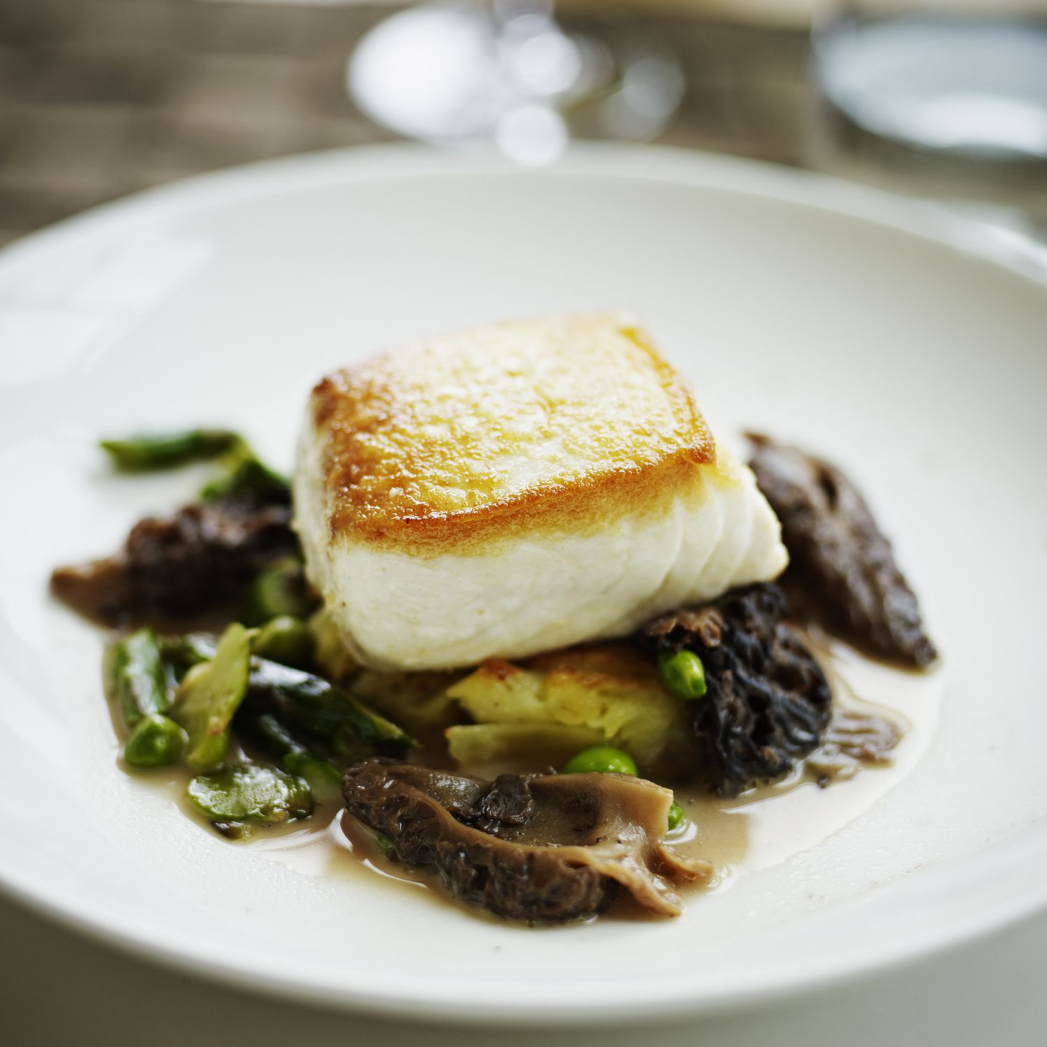 Seared halibut fillet topped on sauteed asparagus and morels