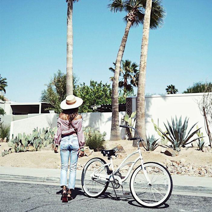 Una mujer con un sombrero visto desde atrás de pie junto a una bicicleta bajo el sol de verano.