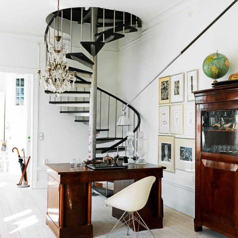 An all-white area underneath a black spiral staircase showing how midcentury modern style can be mixed with other design styles and eras.