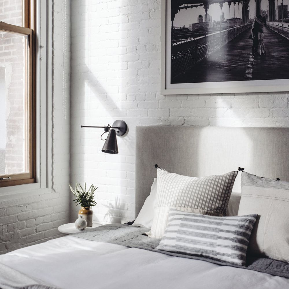 White bedroom with painted brick