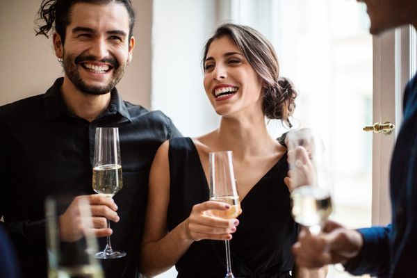 Happy man and woman holding champagne flutes during dinner party at home