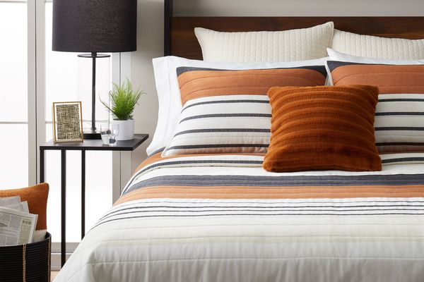 bed with orange striped bedding