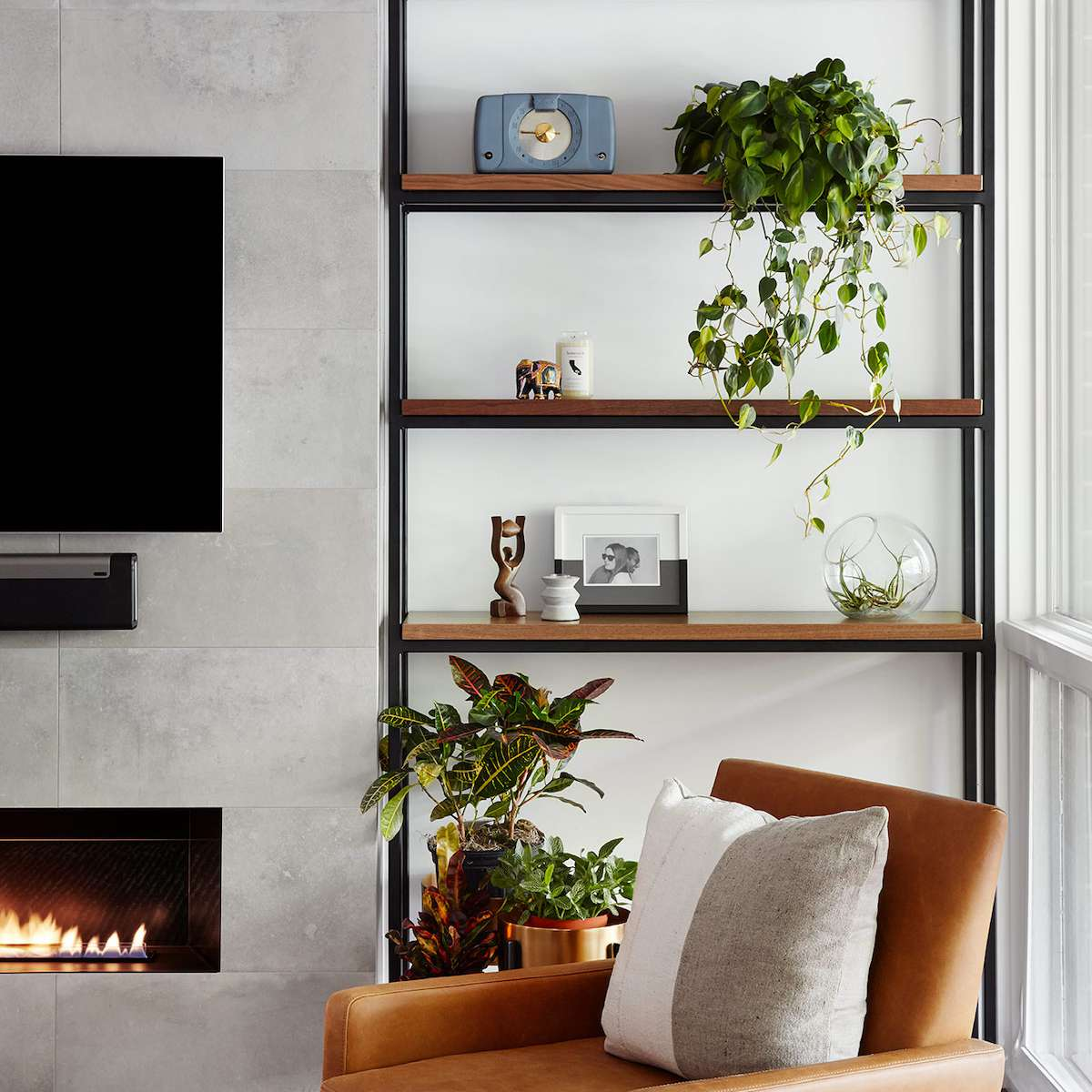 A living room with metal and wooden shelves that have been sparsely decorated