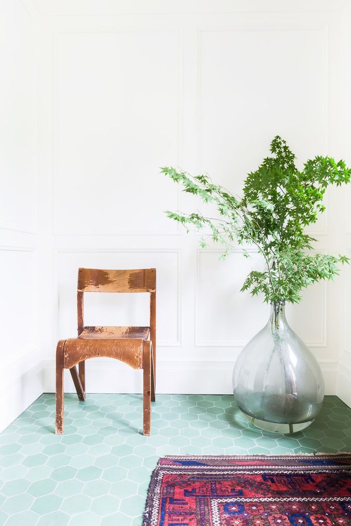 a rustic wood chair and a large green plant in a vase