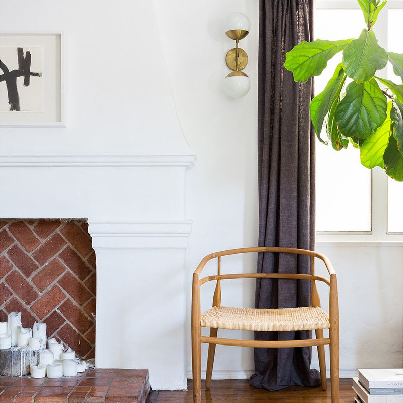 Artfully curated living room corner with fireplace, wood chair, and fiddle leaf fig.