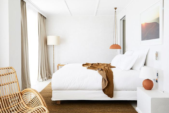An all-white hotel bedroom with orange accents.