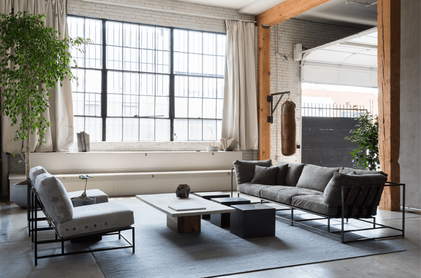An industrial living room with cozy furniture and a punching bag