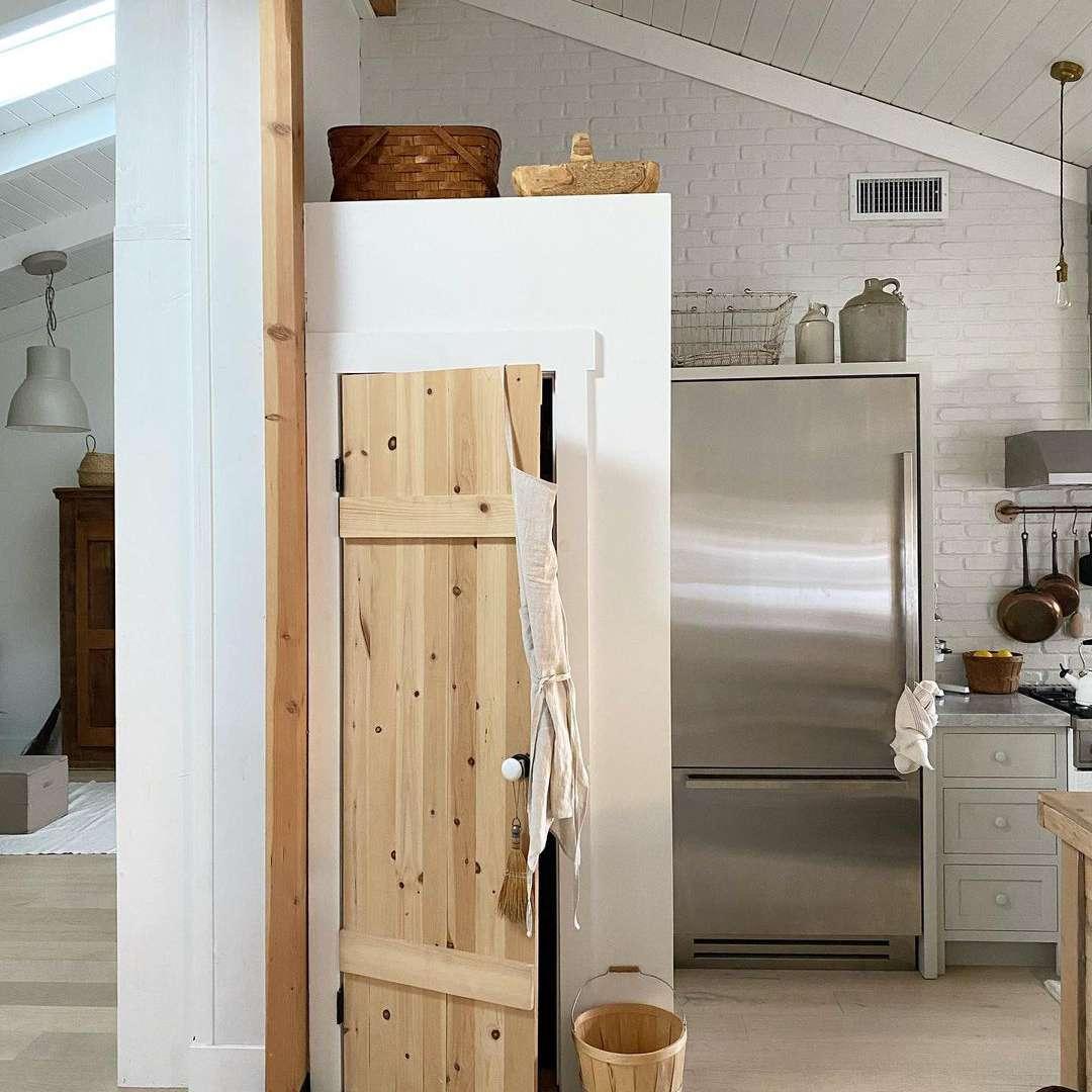 Minimalist kitchen pantry with natural wood door