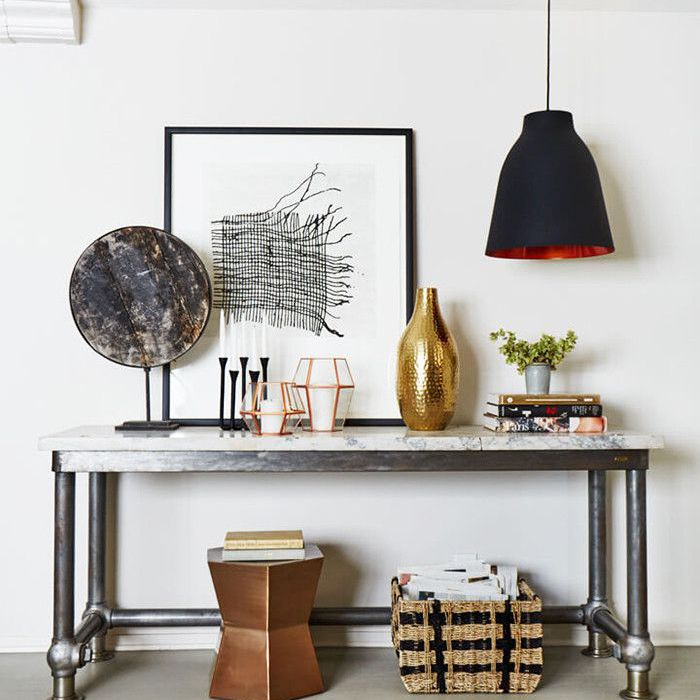a side table with vase, candles, and art