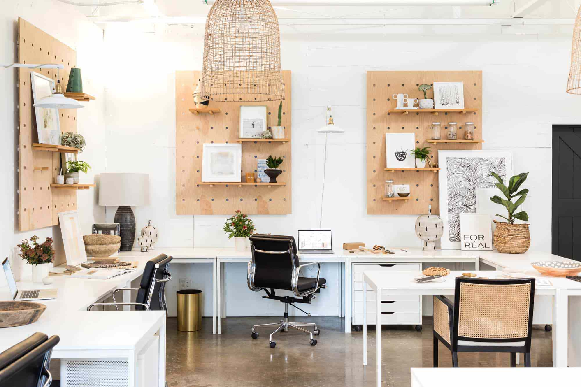 A large workspace with pegboard-lined walls and several under-desk cabinets