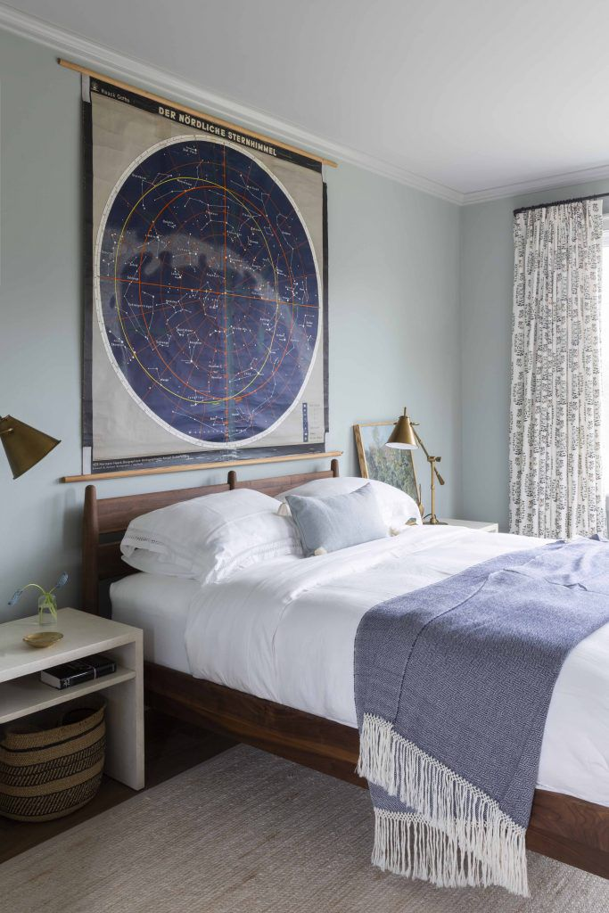 A bedroom with blue blankets, walls, and art