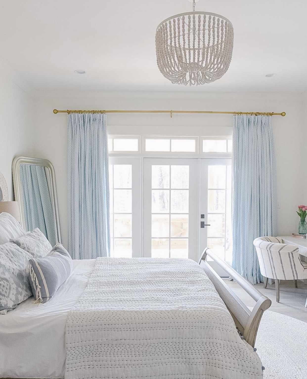 white bedroom with blue drapes