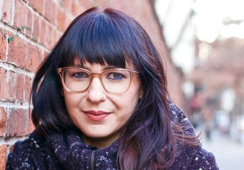 woman with dark hair and glasses next to a brick wall