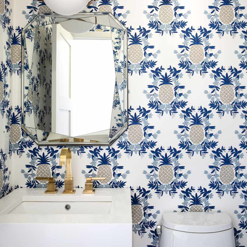 A powder room with bold pineapple print wallpaper lining the walls