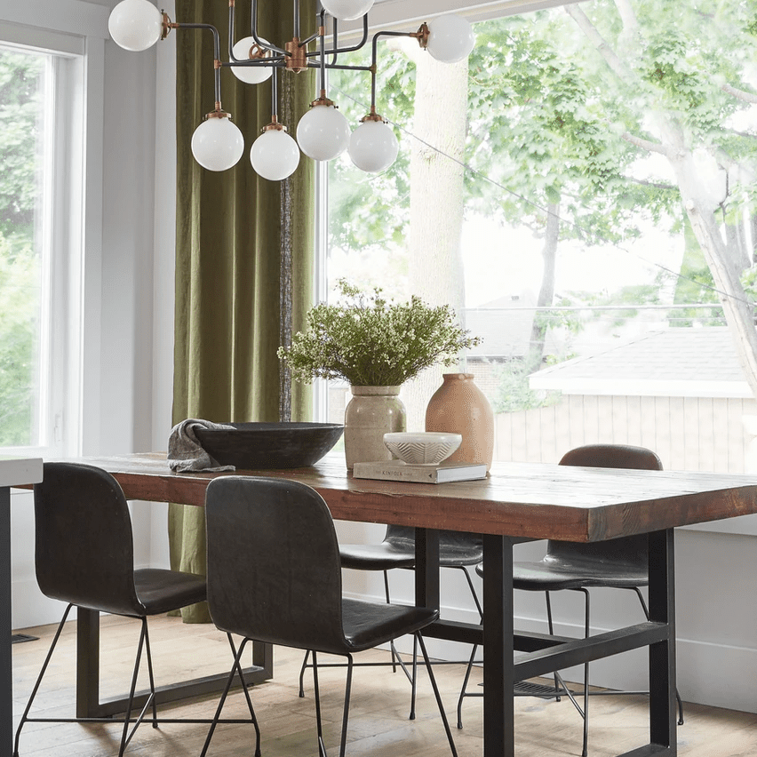 A wooden dining room table topped with vases, bowls, and a book
