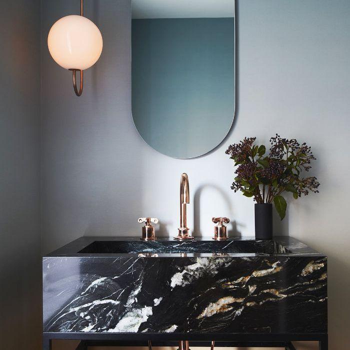 Apartment Lighting Tips: A pendant globe flanks a bathroom mirror