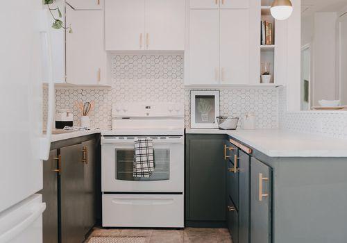 Modern kitchen with white cabinetry, hexagonal tile backsplash