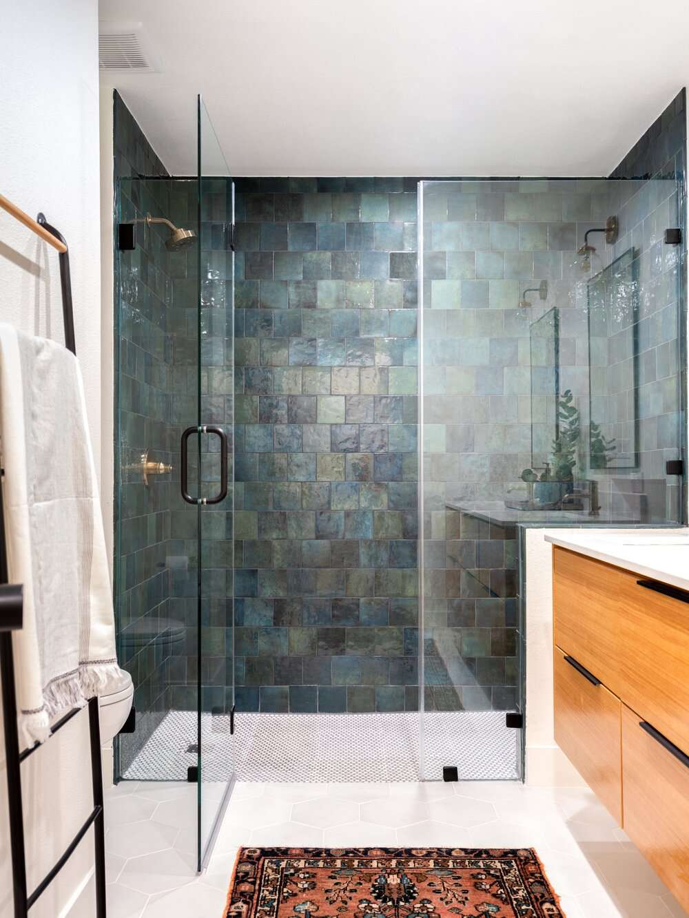 bathroom with green and blue tiled shower