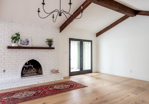 A bare room with hardwood floors and a red printed rug