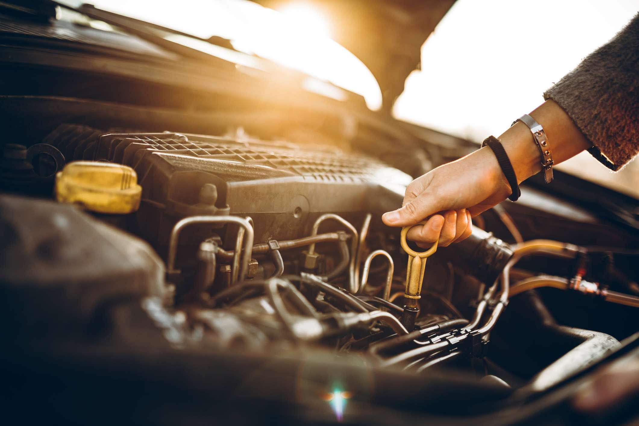 Female hand checks car oil levels