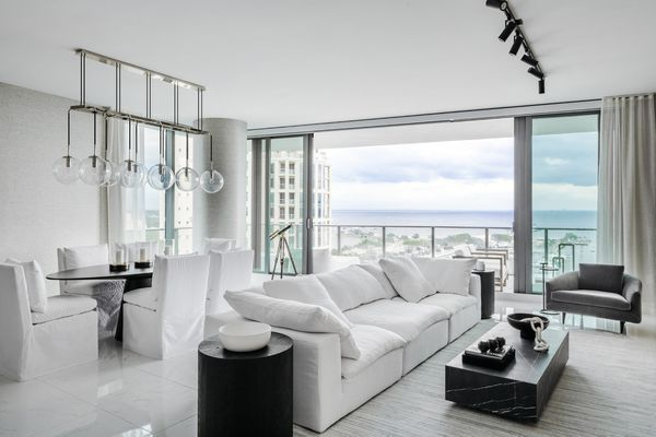 Modern white living room with luxurious accents and beach view.