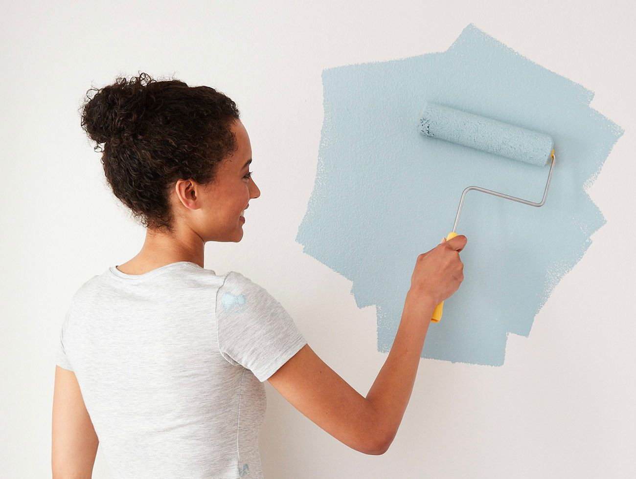 A woman smiling and painting a wall with blue paint using a roller.