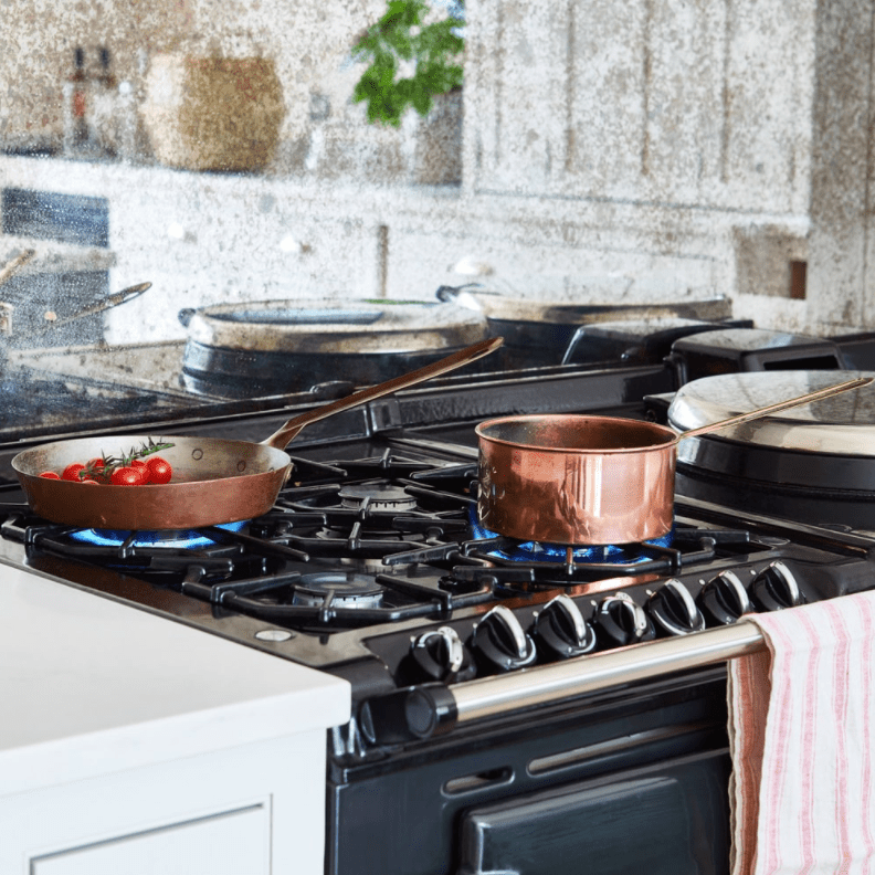 Close up over navy blue stove with copper pots.