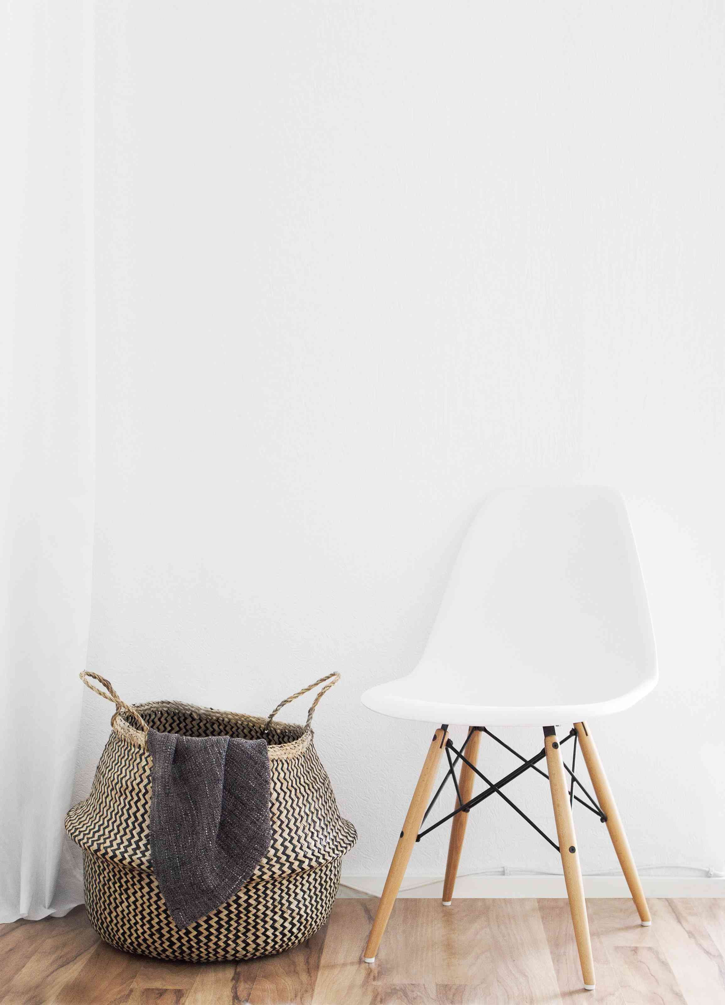 Woven basket next to white chair in entryway