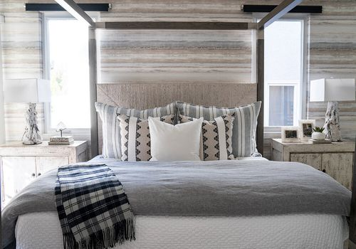 Rustic bedroom with neutral linens and plaid throw.