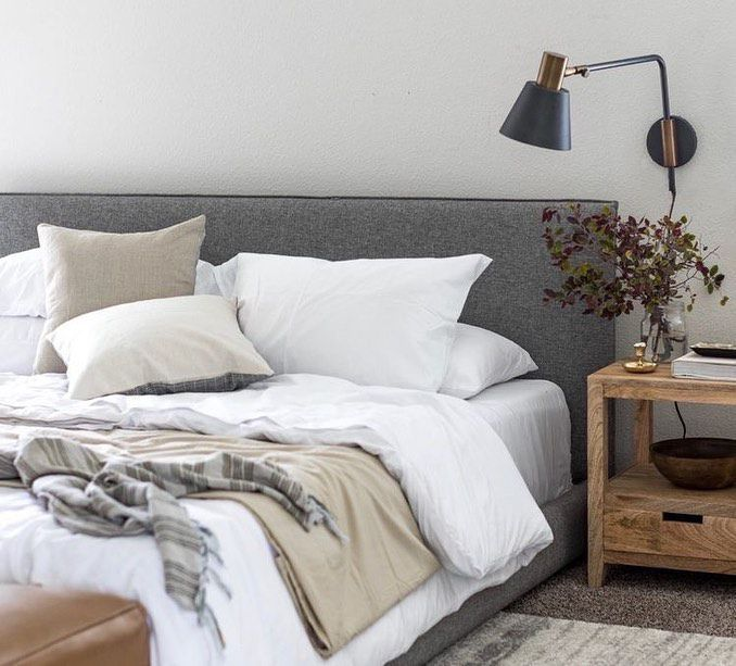 Messy bed with white comforter and gray headboard.